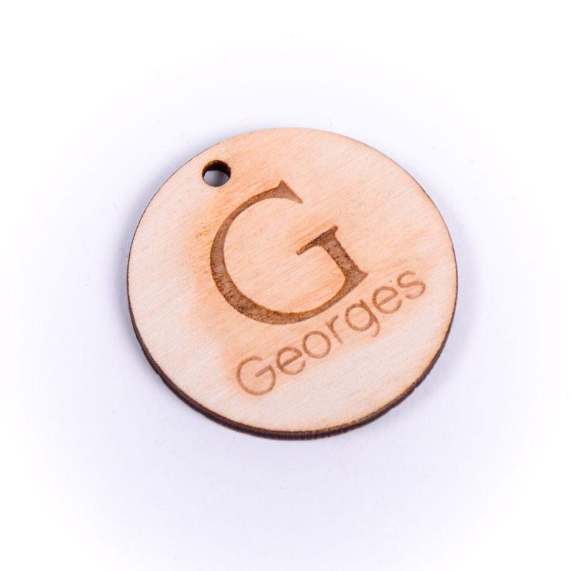 Houten label rond gegraveerd met naam Georges