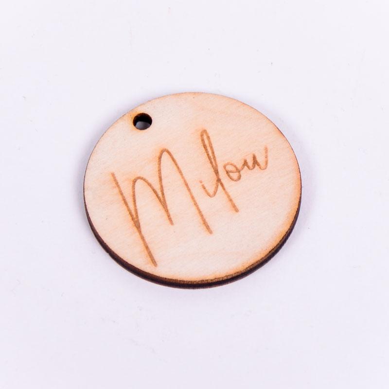 Houten label rond gegraveerd met naam Milou