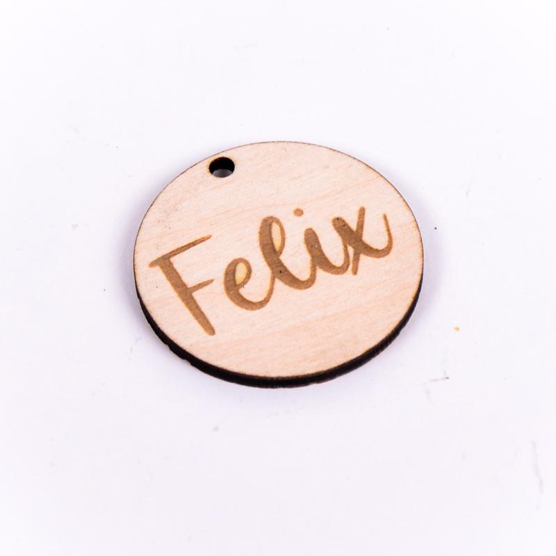 Houten label rond gegraveerd met naam Felix